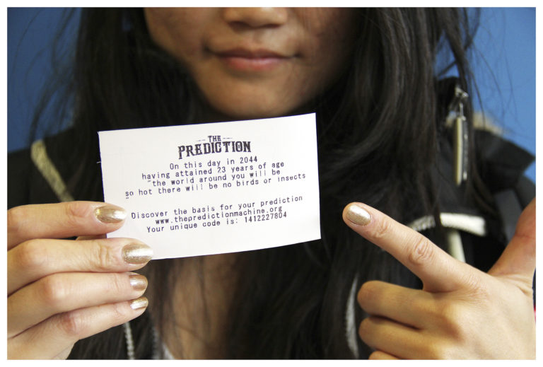 girl holding up a prediction with the code on the bottom