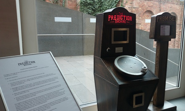 The Prediction Machine and Promises Machine exhibited by a window at Nottingham Contemporary
