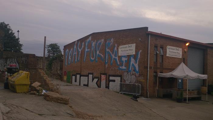 graffiti on a warehouse saying Pray For Rain