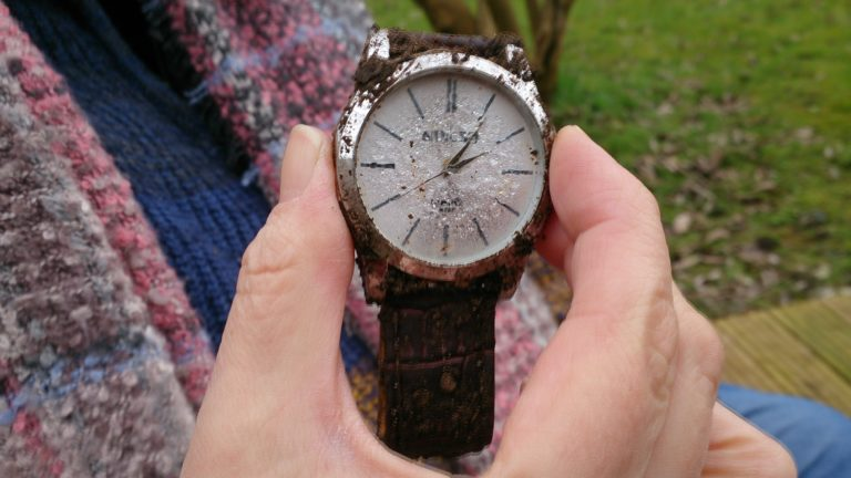 metal watch with condensation on the front and the time 14.06