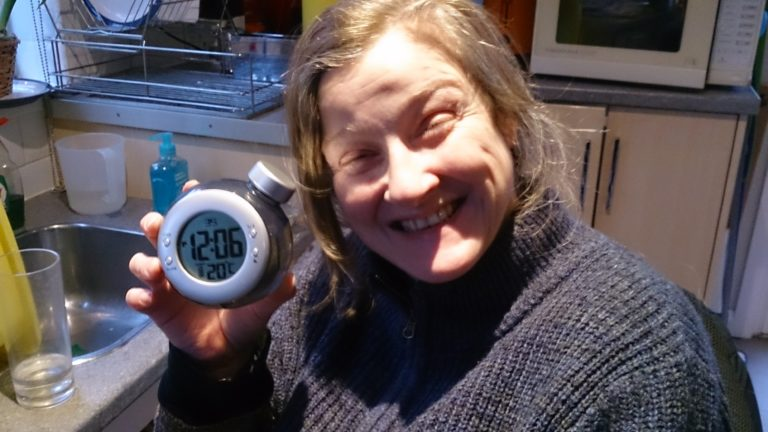 Juliet holding the working water powered clock showing the time 12.06