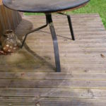 a round metal table and blue and white lines drawn around shadows on the decking
