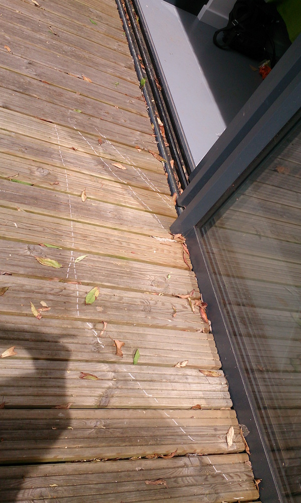 white lines drawn around shadow of the window on the decking window