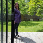 Rachel standing at the windows of the studio