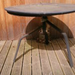 round metal table with white lines drawn on teh decking