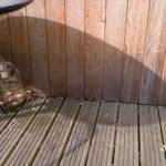 shadow of the round table and white lines drawn on the decking and wooden wall of the studio