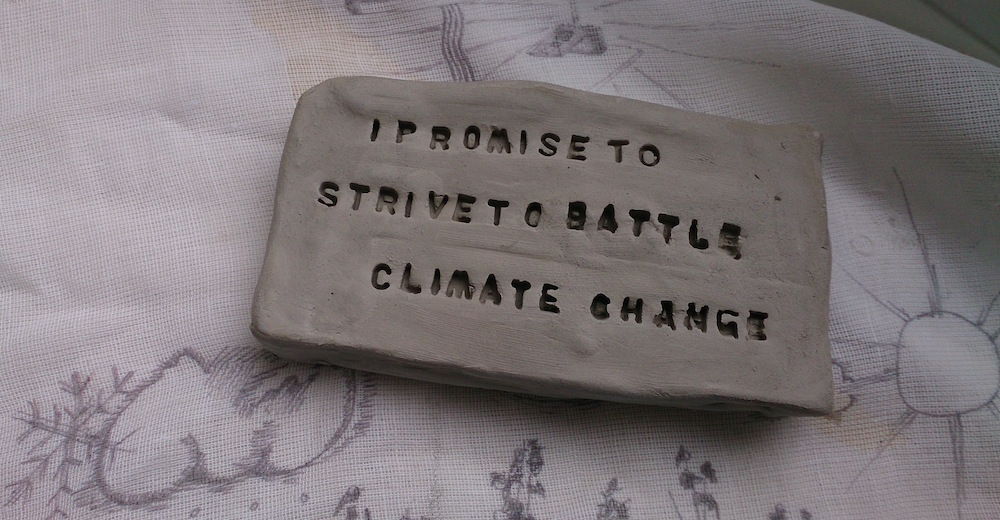 a small rectangular grey clay tablet with 'I promise to strive to battle climate change' embossed in the clay, on a muslin fabric with drawings of clouds and the sun printed on it