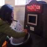 a girl turning the handle to power The Prediction Machine at Polka Theatre