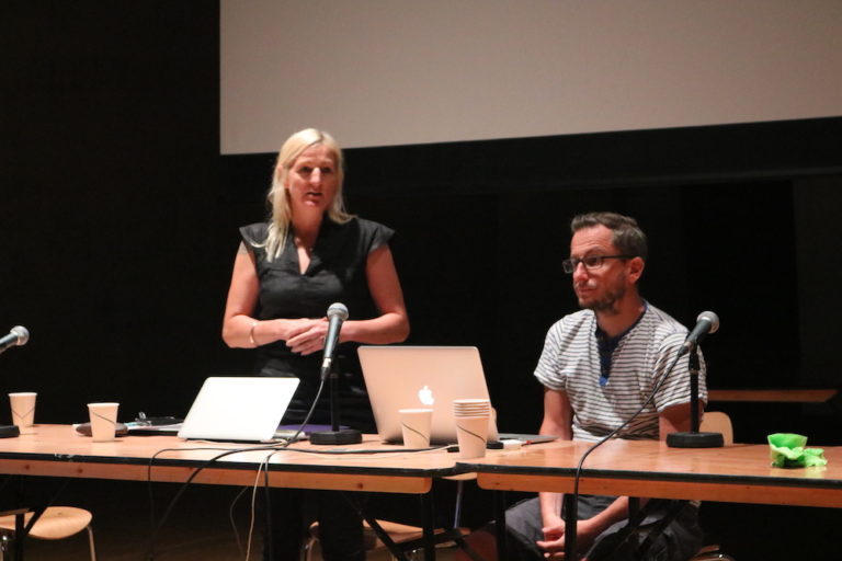 Caroline and Matt presenting at a table with laptops and a screeen behind them