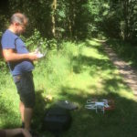 Matt and the drone on a path in the forest with sunlight behind him