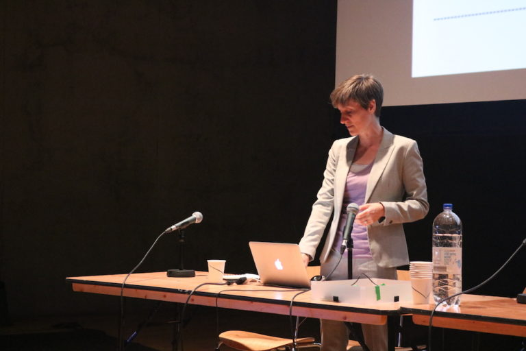 Esther presenting at a table with a laptop and microphone