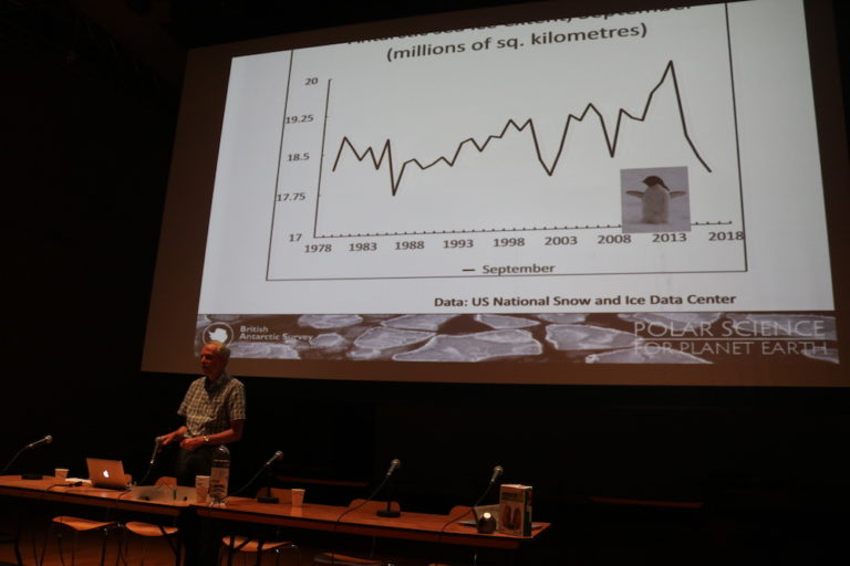 a graph of sea ice levels and John presenting at a row of tables with mircrophones