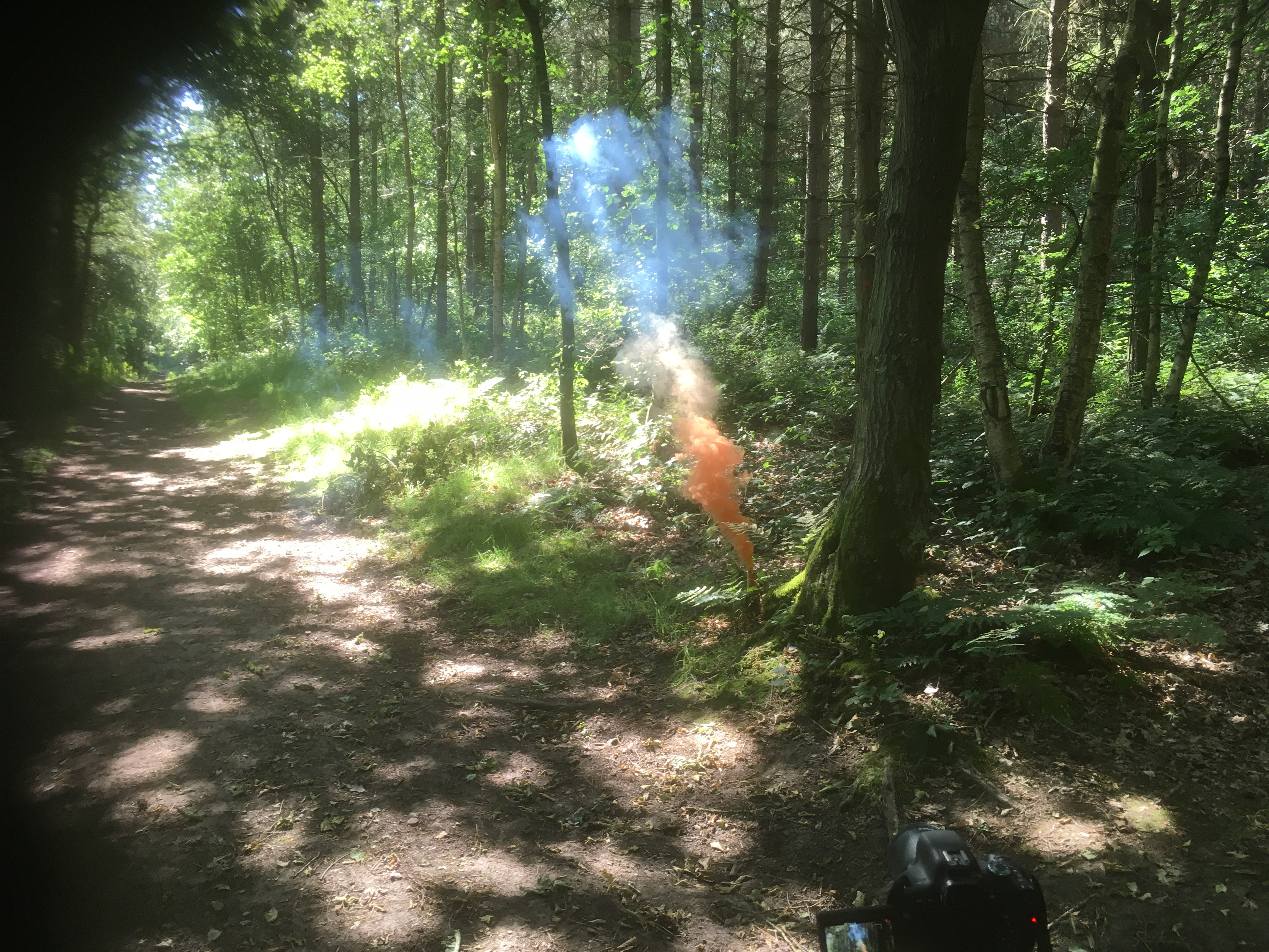 orange and blue smoke rising by the path