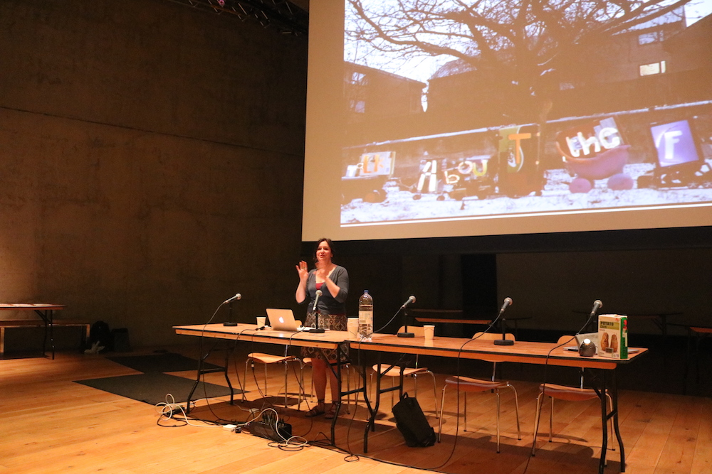 Rachel presenting at a table with mricrophones and a laptop with a projection on a large screen behind her of the video haiku from the blossoms project