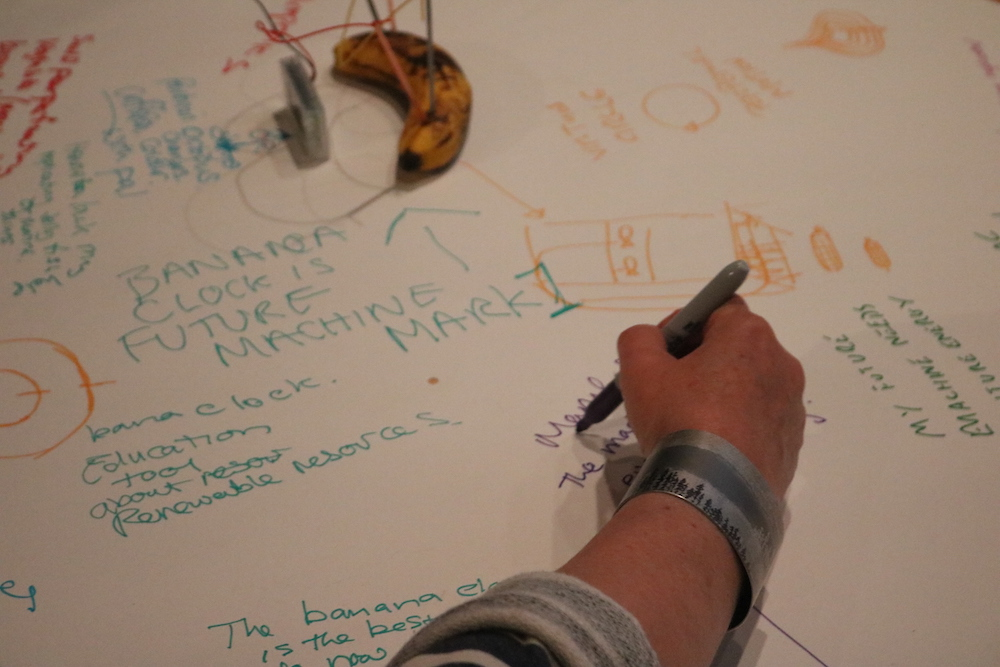 a participant in the workshop writing ideas on paper with the banana clock