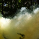 a large yellow smoke cloud blocking out the trees