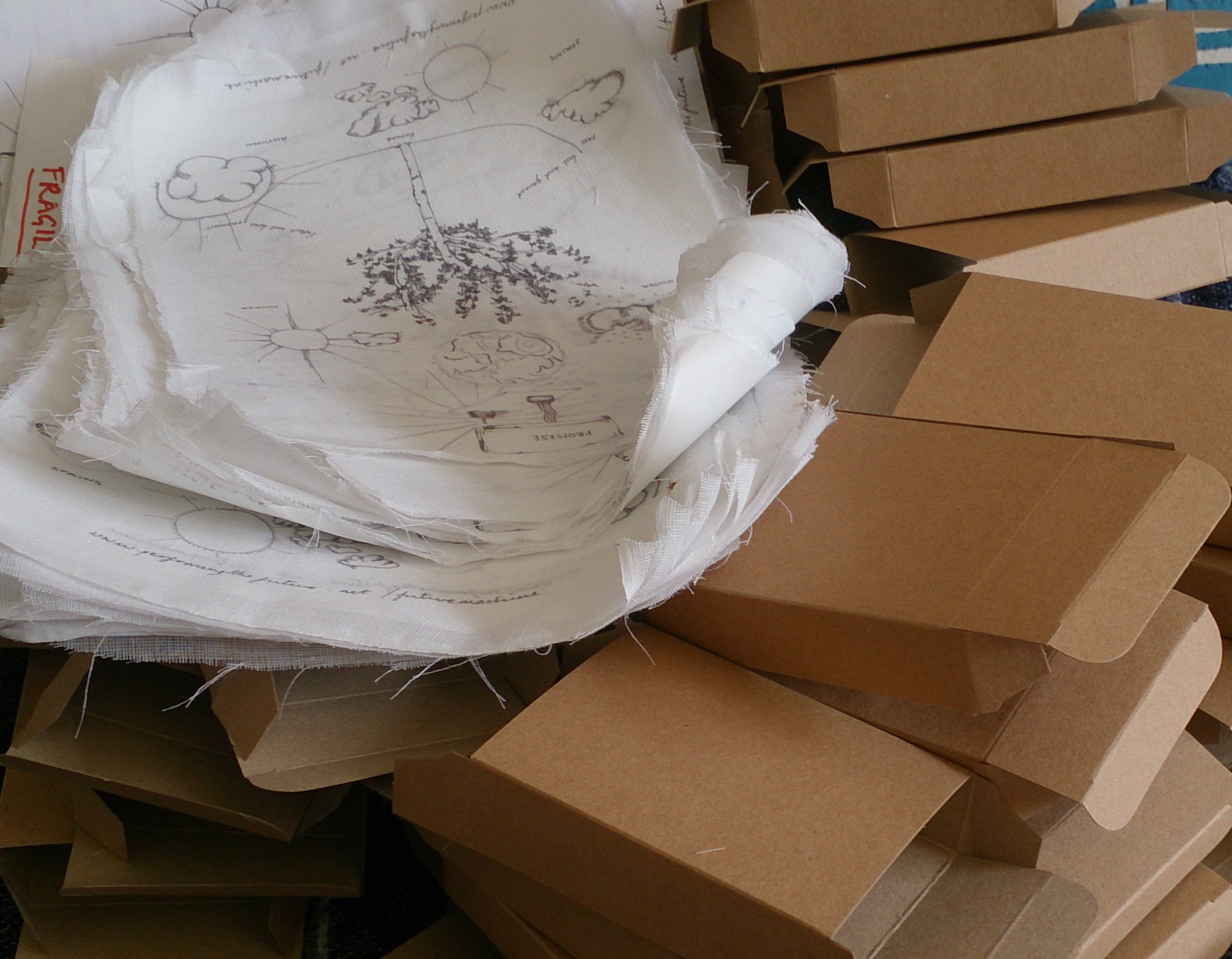 a pile of cardboard boxes and muslin with a drawing printed on them